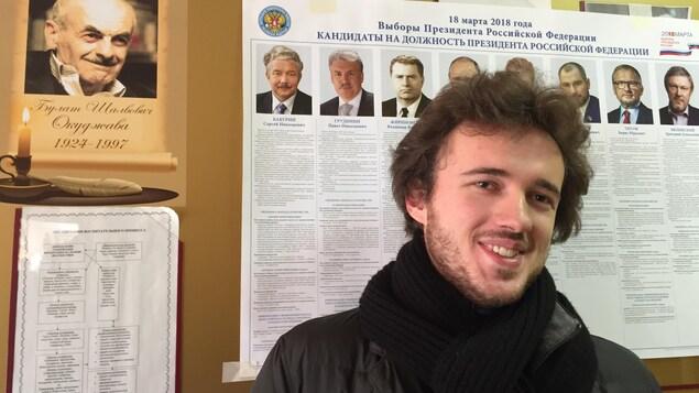 Un électeur russe pose devant les photos des candidats à l'élection présidentielle.