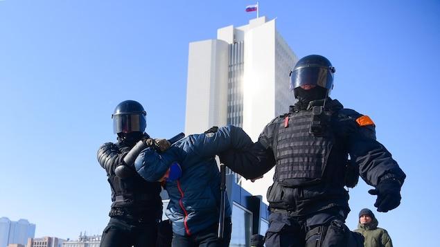 Deux policiers encadrent un manifestant. L'un le tient par le bras, l'autre lui tient la tête penchée.