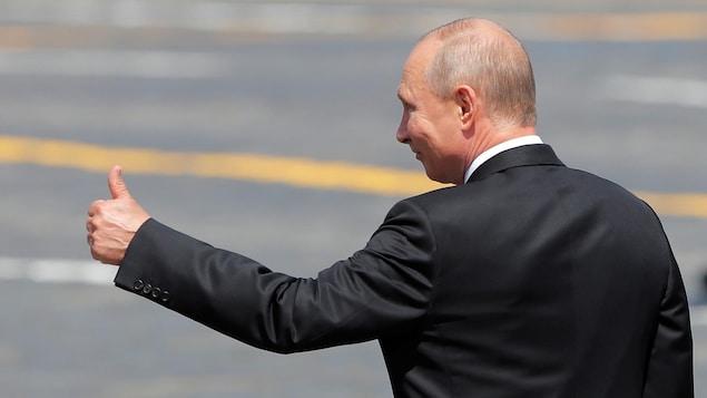 Plan moyen de Vladimir Poutine, de biais, le pouce en l'air.