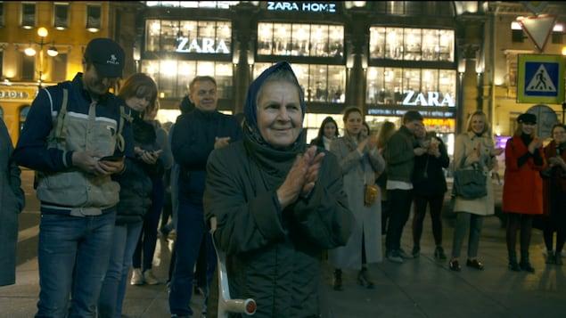 Une foule chante et tape des mains dans la rue.