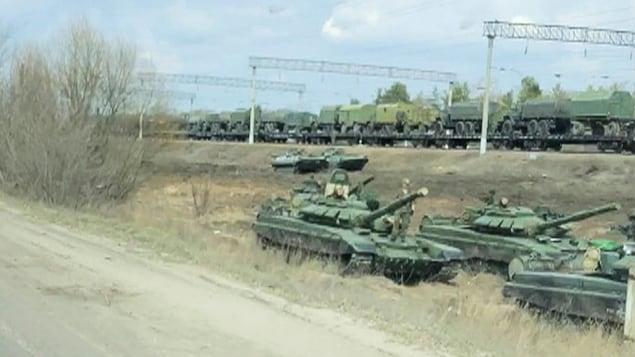 Des tanks sur le bas-côté de la route et, en arrière-plan, des véhicules militaires montés sur un train.