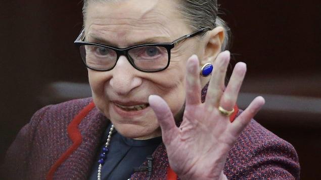 La femme sourit et fait un signe de la main.