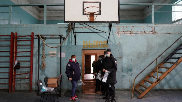 Des militaires attendant, masqués, de voter dans un gymnase décati.