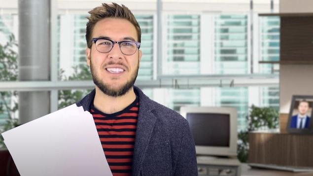 Ryan George jouant le rôle d'un scénariste dans une des vidéos. Il porte des lunettes et a un script dans les mains.