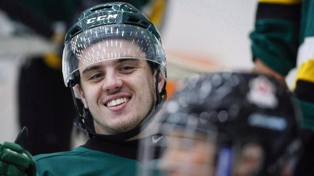 Ryan Straschnitzki souriant avec un casque de hockey.