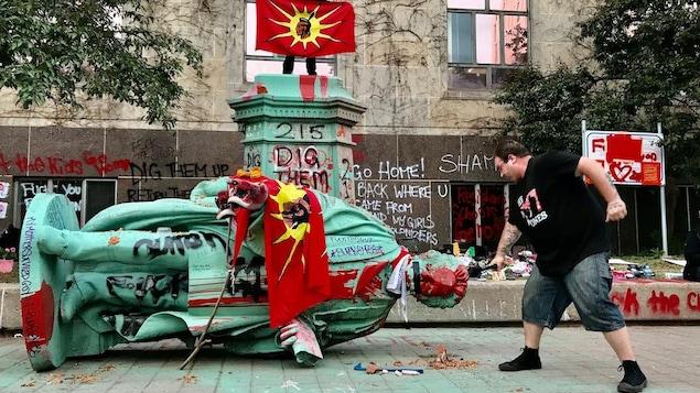 Una persona junto a una estatua derribada en gesto de protesta.