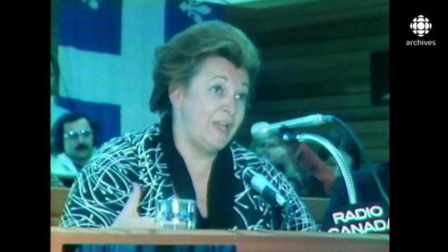 Lise Payette s'exprimant au micro, dont un identifié comme Radio-Canada