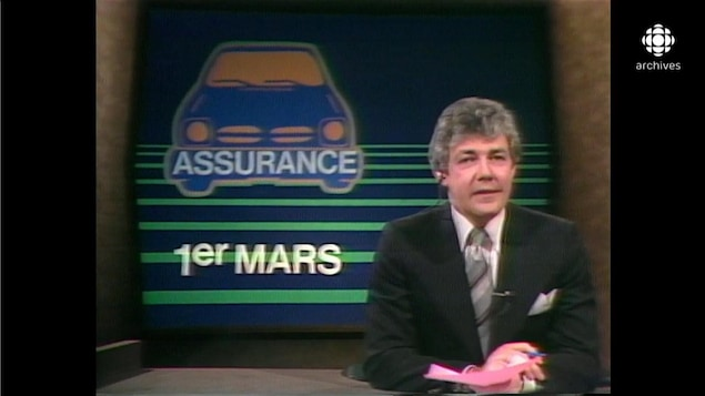 Normand Harvey devant une mortaise illustrant une automobile avec les inscriptions Assurance et 1er mars