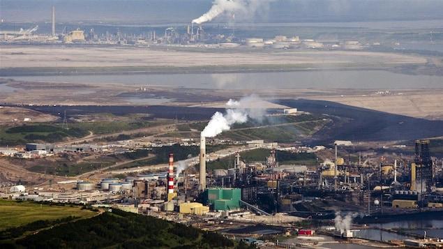 دخان يتصاعد من منشآت لاستخراج النفط من الرمال الزفتية قرب فورت ماك موراي في شمال شرق مقاطعة ألبرتا في غرب كندا.