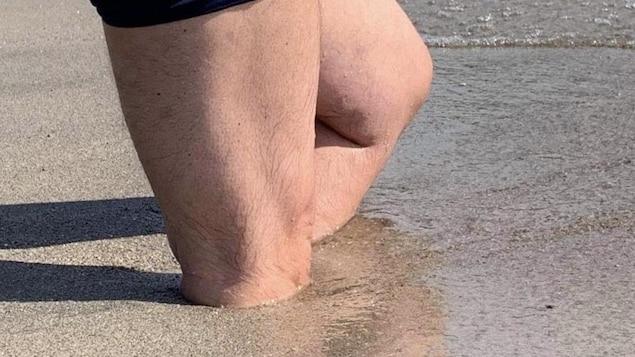 Les jambes d'un homme enlisées dans le sable jusqu'aux genoux.