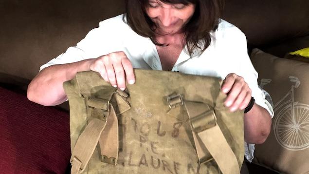 Une femme aux cheveux bruns contemple un vieux sac à dos militaire.
