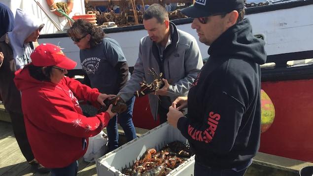 Michael Sack et d'autres membres de sa communauté examinent des homards sur un quai.