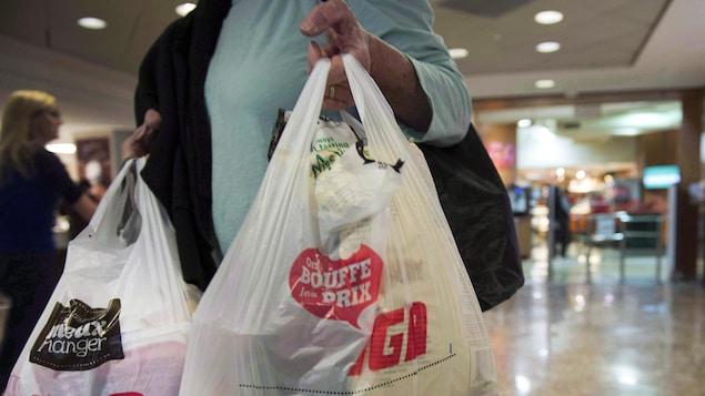 Une femme tient des sacs de plastique à la main.