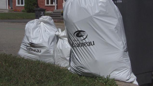 Des sacs de poubelle blancs avec le logo de la ville de Gatineau, placés sur le bord d'une rue.