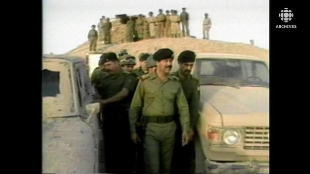 Saddam Hussein marchant entre deux véhicules suivi par des militaires.