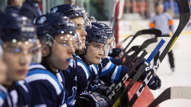 Des joueurs des Saguenéens de Chicoutimi sont assis sur le banc.