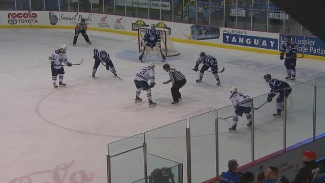 Des joueurs s'affrontent sur la glace.