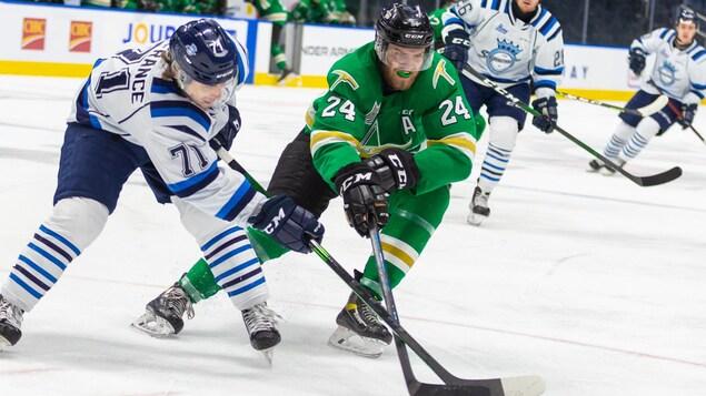 Deux joueurs de hockey se disputent le disque.
