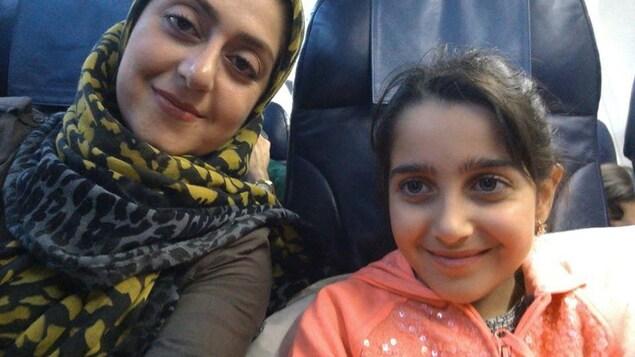 Une femme avec un hijab et sa fille sourient dans un avion.