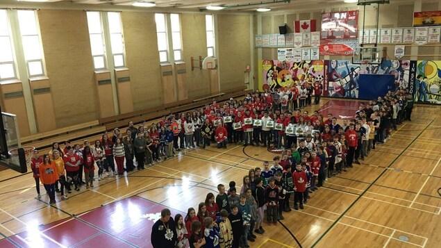 Des centaines de jeunes debout dans un gymnase en formation de H.