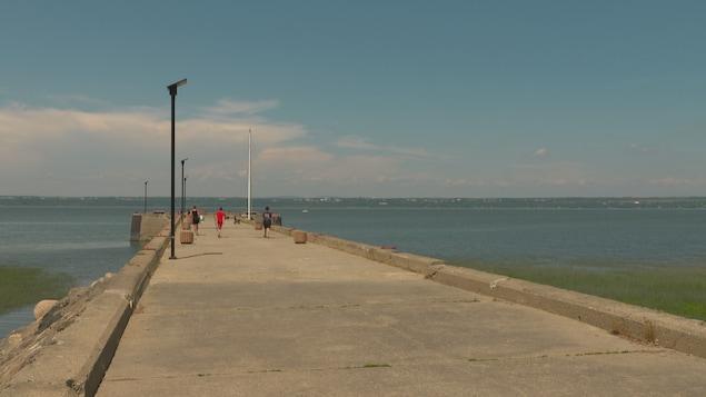 Le quai de Saint-Antoine-de-Tilly avec trois pêcheurs qui marchent vers la pointe. On voit le fleuve Saint-Laurent