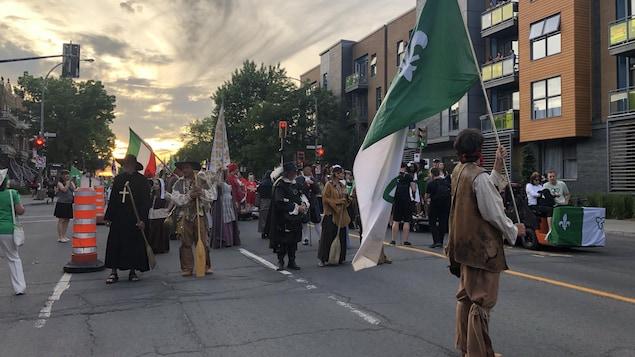 Des participants en costumes s'apprêtent à marcher rue Saint-Denis à Montréal.