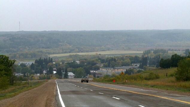 Une route qui descend vers un village au coeur d'une vallée verdoyante.