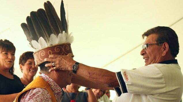 Un homme dépose une coiffe autochtone sur la tête d'Allan (Chicky) Polchies, le nouveau chef de la communauté malécite de Saint-Mary, au Nouveau-Brunswick.