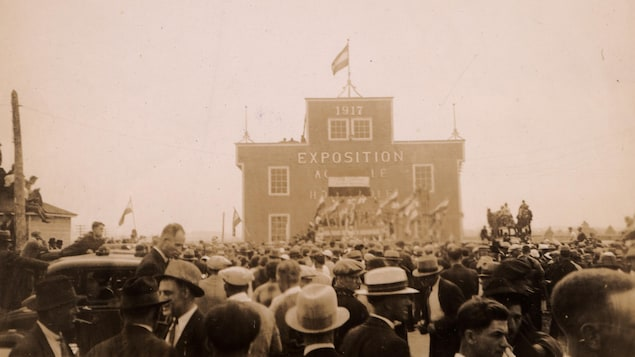 Photo en noir et blanc ou de nombreuses personnes circulent devant le pavillon principal de l'Expo agricole de Saint-Pascal.