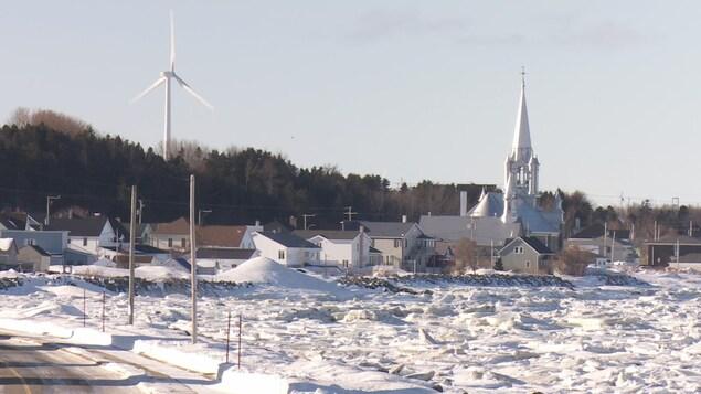Village sous la neige avec l'église et une éolienne
