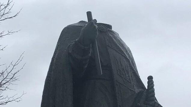 Une statue sans tête avec un ciel nuageux