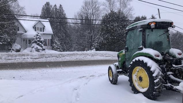 Un tracteur devant une maison à Sainte-Anne-des-Lacs.