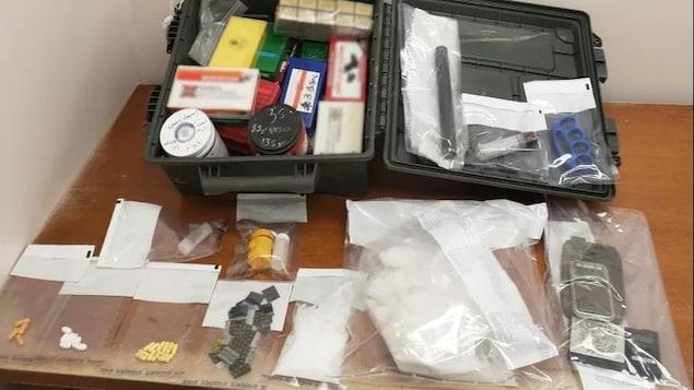 Une mallette avec son contenu et d'autres objets déchargés sur une table.