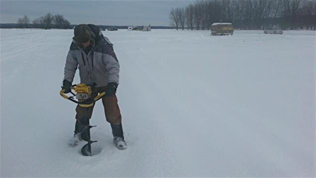 Un homme utilise une tarière à essence pour percer un trou dans la glace