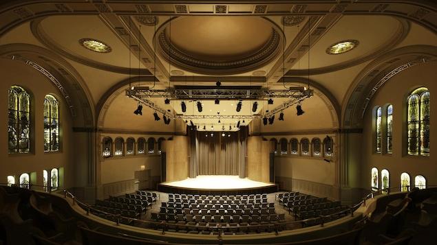 Vue de la scène de la salle Bourgie, et de nombreuses rangées de sièges, à partir du balcon.