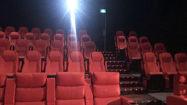 Une salle de cinéma dotée de fauteuils rouges.