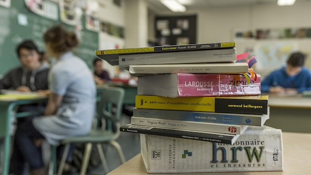 Plusieurs livres empilés dans une classe avec en arrière-plan des élèves.