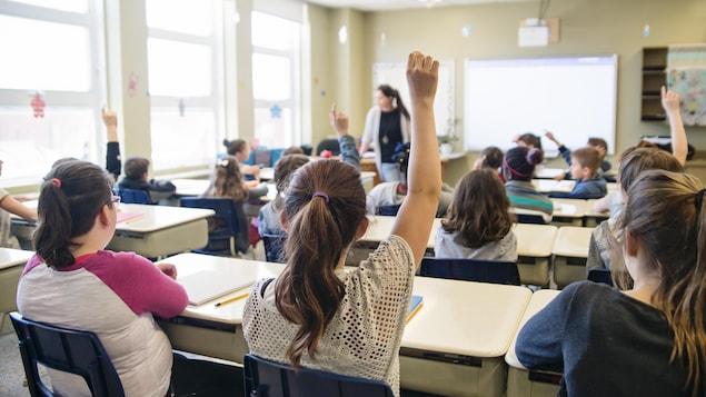 Des étudiants lèvent la main pour répondre à la question de la professeure dans une salle de classe.
