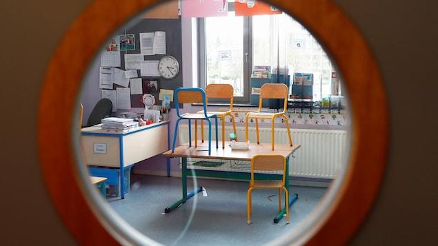 Une salle de classe vide photographiée à travers l'œil magique d'une porte.