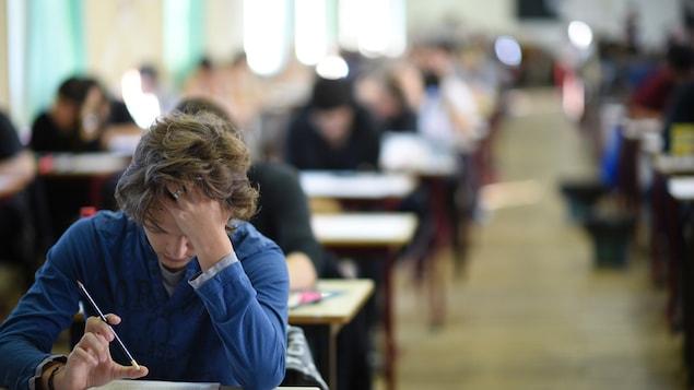 Un adolescent est penché sur son bureau dans une salle de classe.