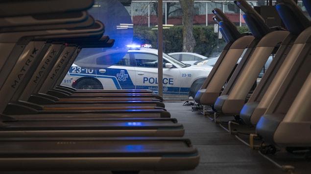 Des appareils dans un gymnase et, à l'extérieur, une voiture de police.