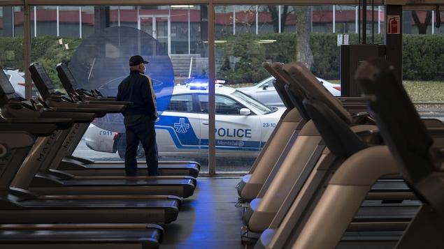 Un policier donne une contravention à un automobiliste devant un gymnase, un homme à l'intérieur regarde.