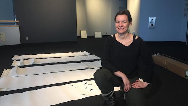 Une femme est assise devant des papiers blancs et pose à la caméra.
