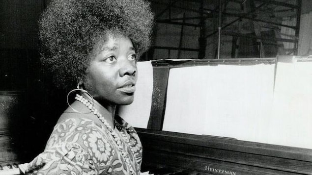 L'artiste est assise devant un piano.