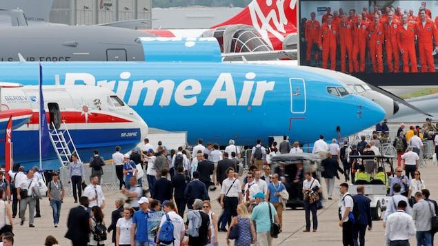 Des visiteurs défilent devant des avions en démonstration.
