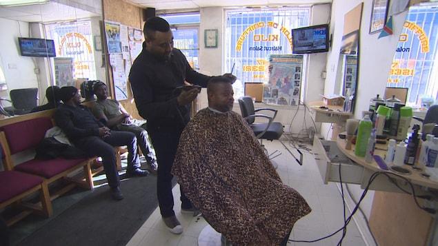 Deux clients attendent assis. Un client sur une chaise se fait couper les cheveux par un coiffeur qui tient une tondeuse dans la main gauche.