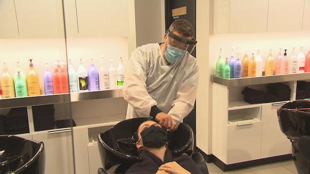 Un coiffeur lave les cheveux d'une cliente.