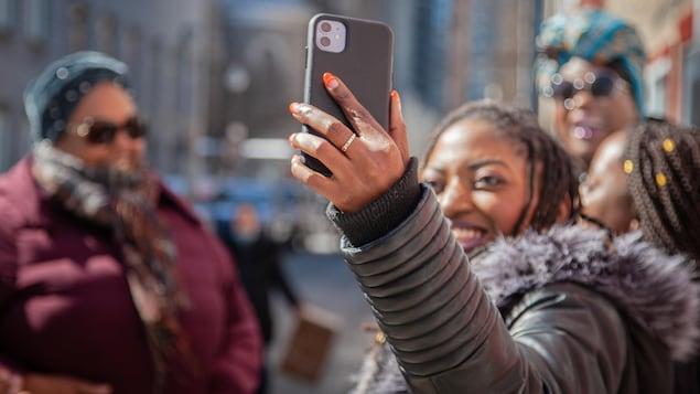 Plaquie tient un cellulaire dans sa main et prend une selfie en compagnie d'autres femmes du groupe.