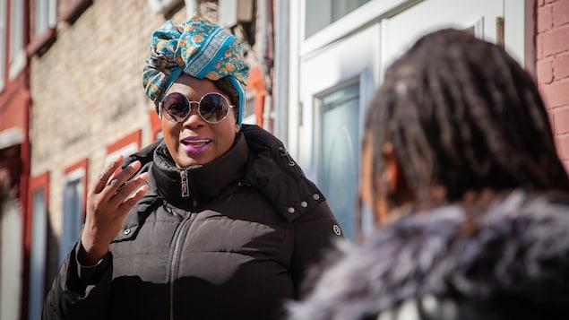 Meika discute avec Plaquie dans la rue. Elle porte un foulard bleu sur la tête et des lunettes de soleil rondes.