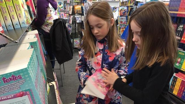 Deux jeunes filles bouquinent à un salon du livre.